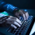 Hands of developer working on computer in the dark