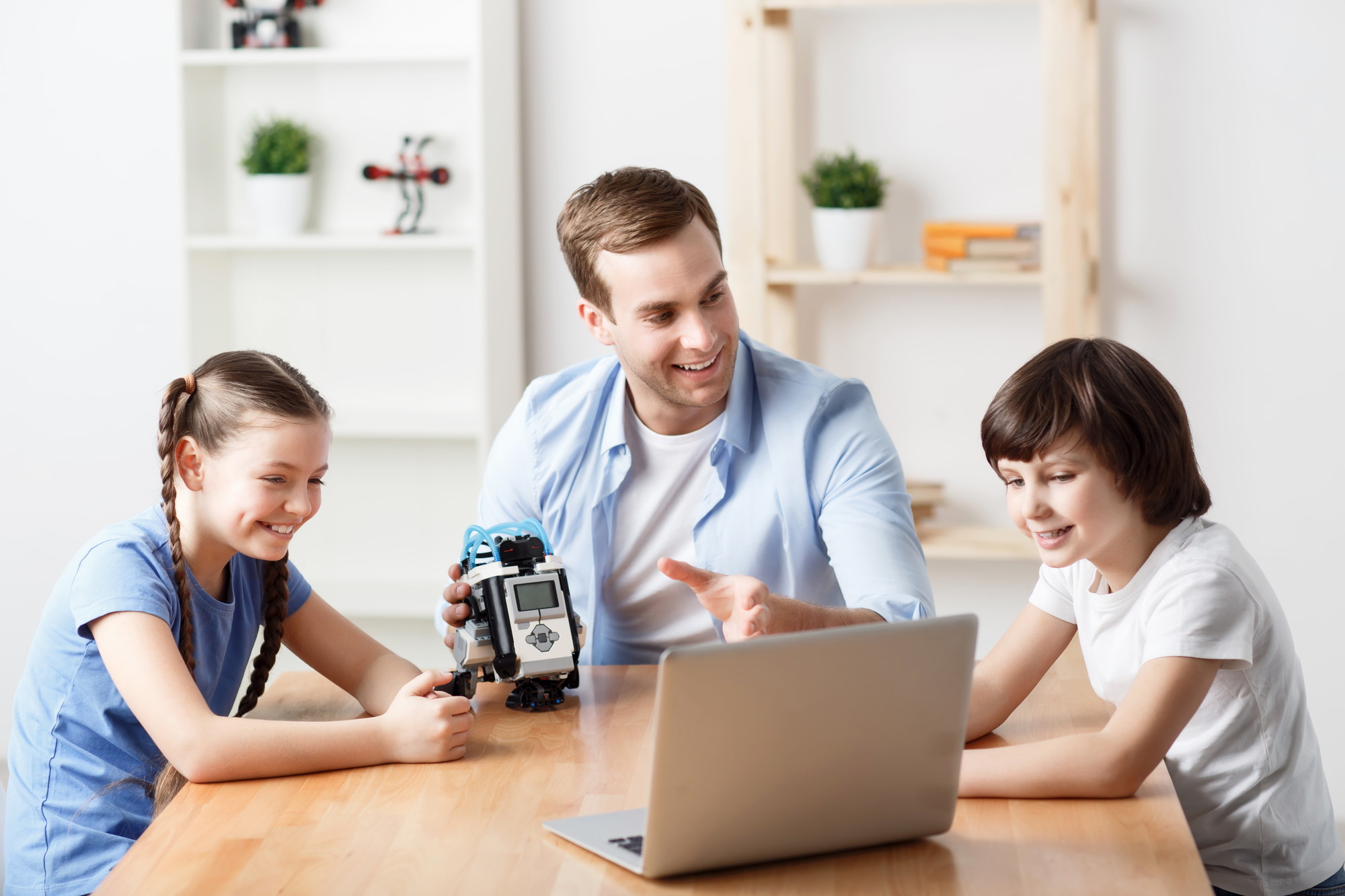 Have a look. Cheerful delighted handsome smiling father holding robot and sitting at the table with his children while using laptop