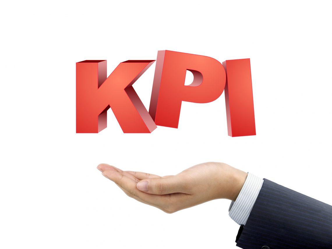 businessman's hand holding KPI words over white background