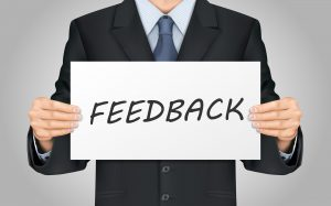 close-up look at businessman holding feedback poster
