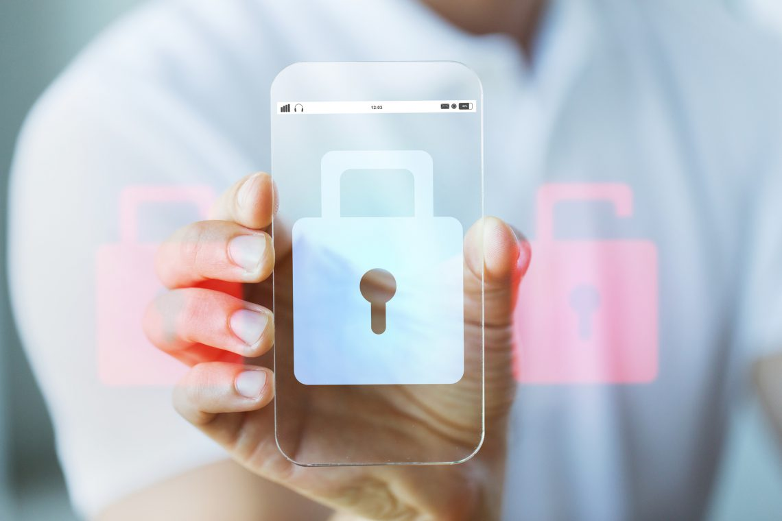 business, technology, security, protection and people concept - close up of male hand holding and showing transparent smartphone with lock icon on screen