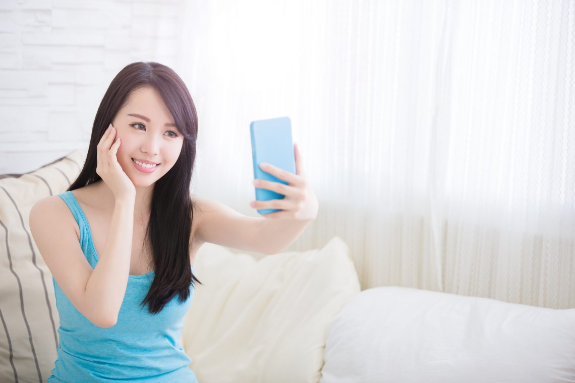 young woman is taking selfies in living room at home, asian
