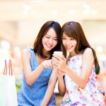 Happy woman looking at smart phone at  shopping mall